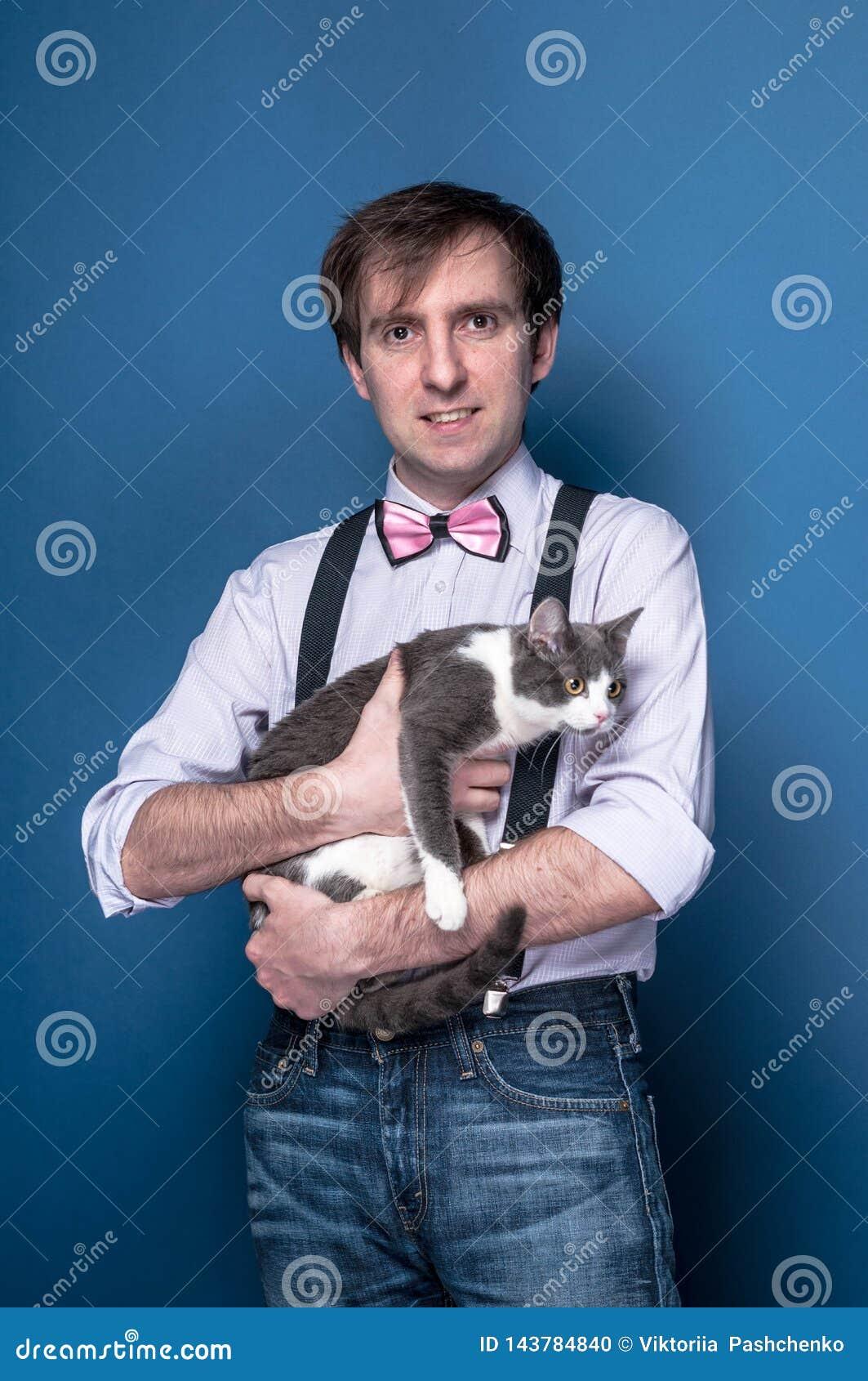 Homem na camisa, no suspender e no laço cor-de-rosa olhando a câmera, sorrindo e guardando o gato cinzento bonito