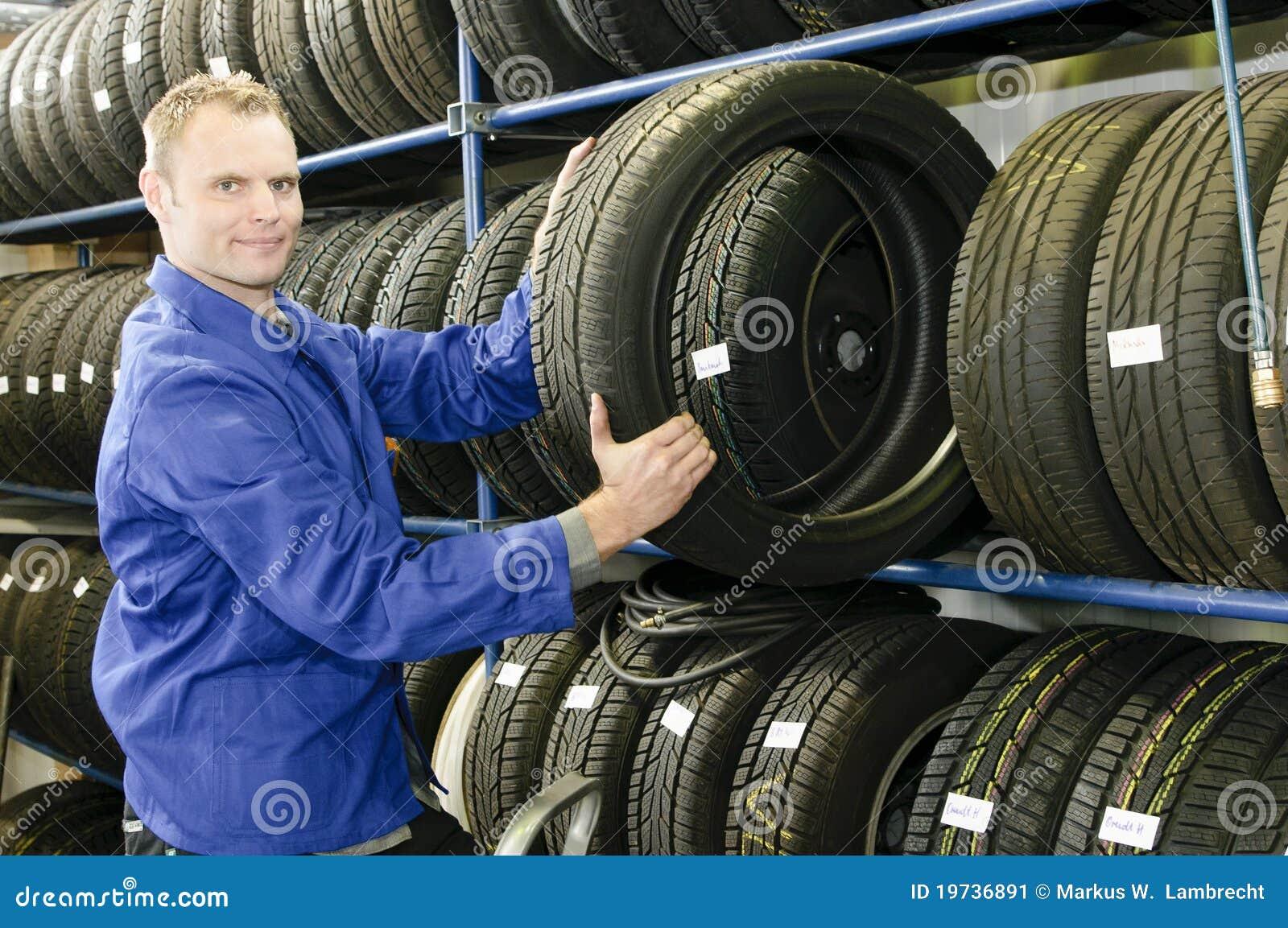 Homem na loja do pneu com um pneu