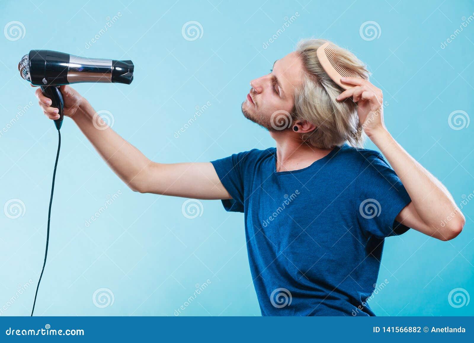 Homem na moda com secador de cabelo