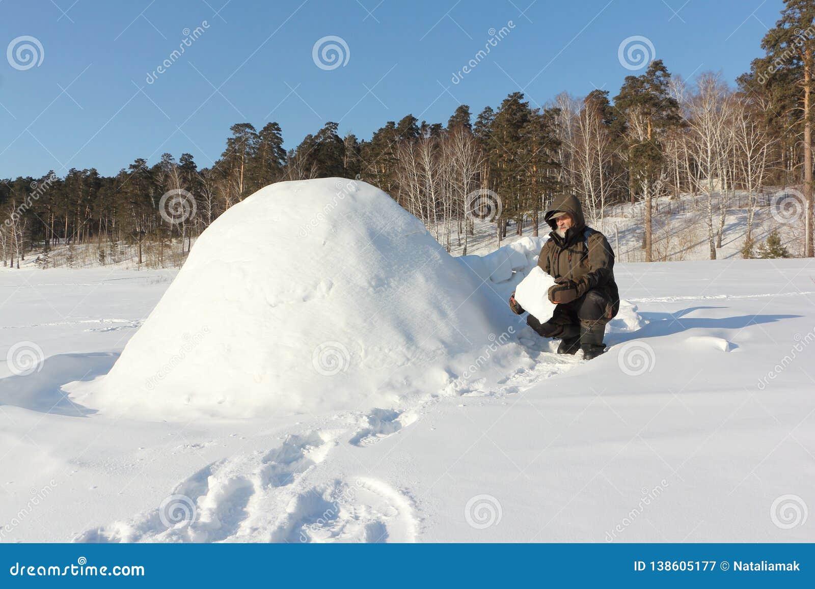 Homem na roupa morna que constrói um iglu em uma clareira nevado no inverno, Sibéria, Rússia