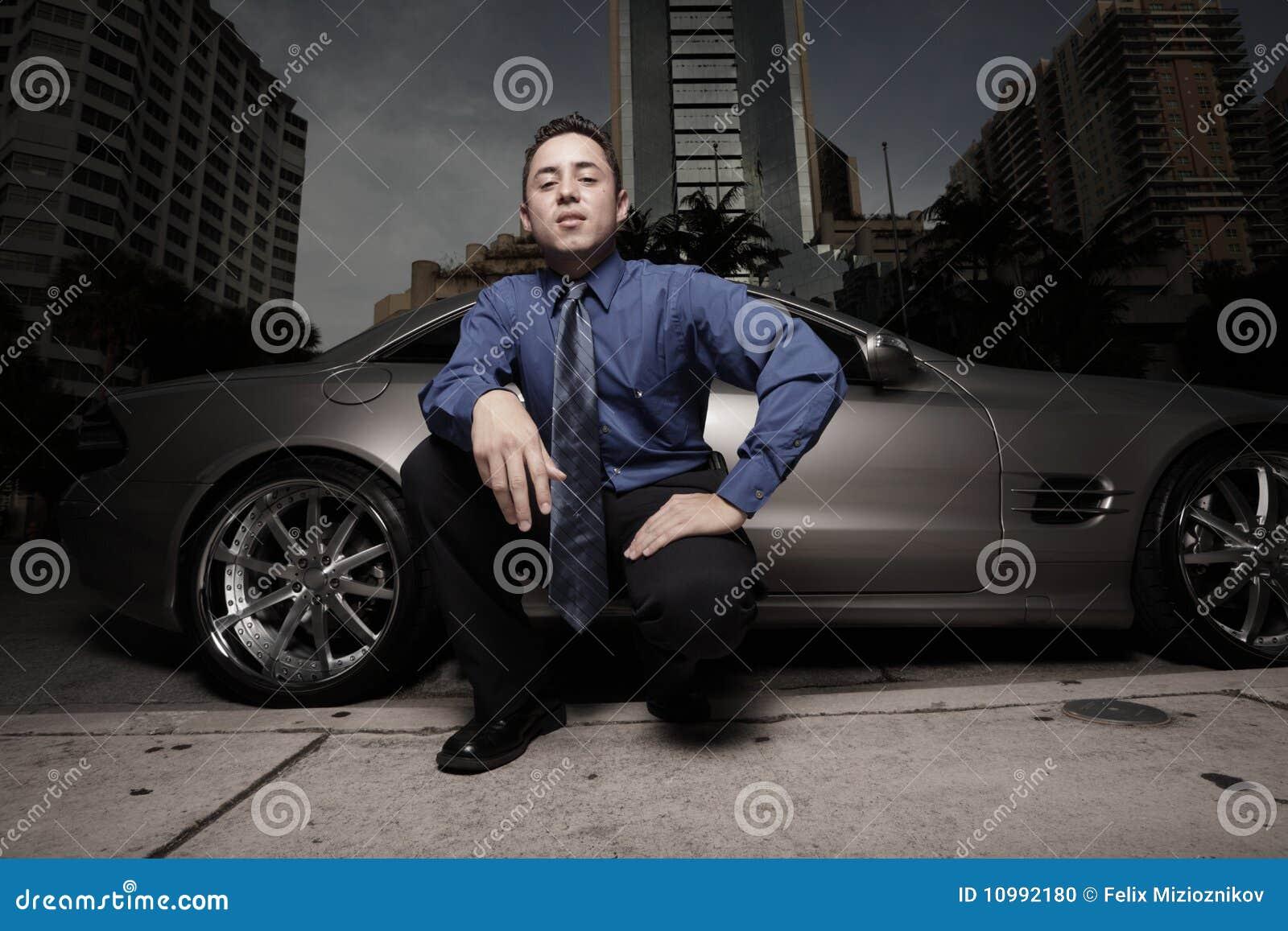 Homem na rua com seu carro de esportes do luxo