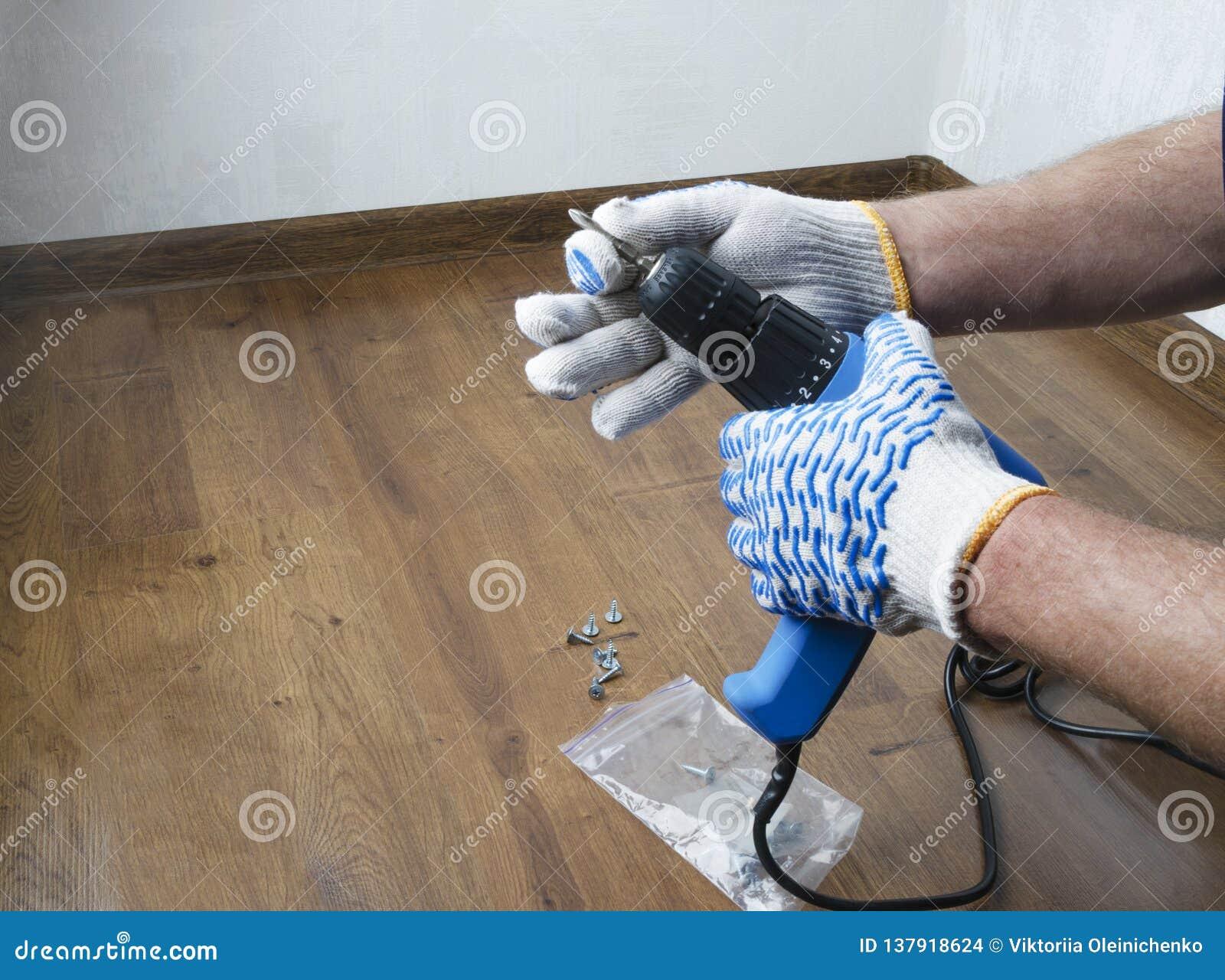 Homem nas luvas que preparam-se para a renovação, pondo em algum bocado de broca Conceito dos reparos na casa