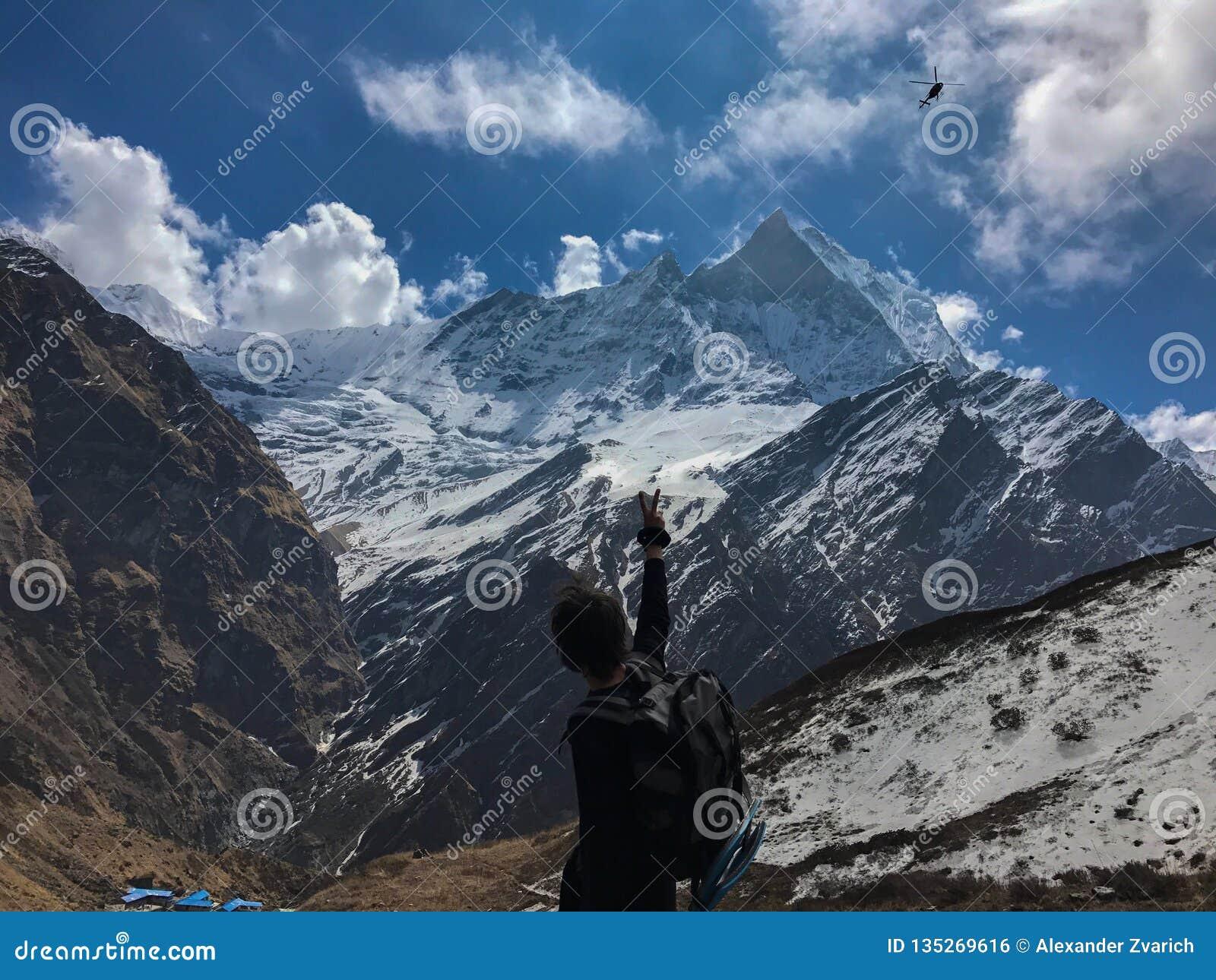 Homem nas montanhas que acenam ao helicóptero que passa perto Nepal, circuito de Annapurna