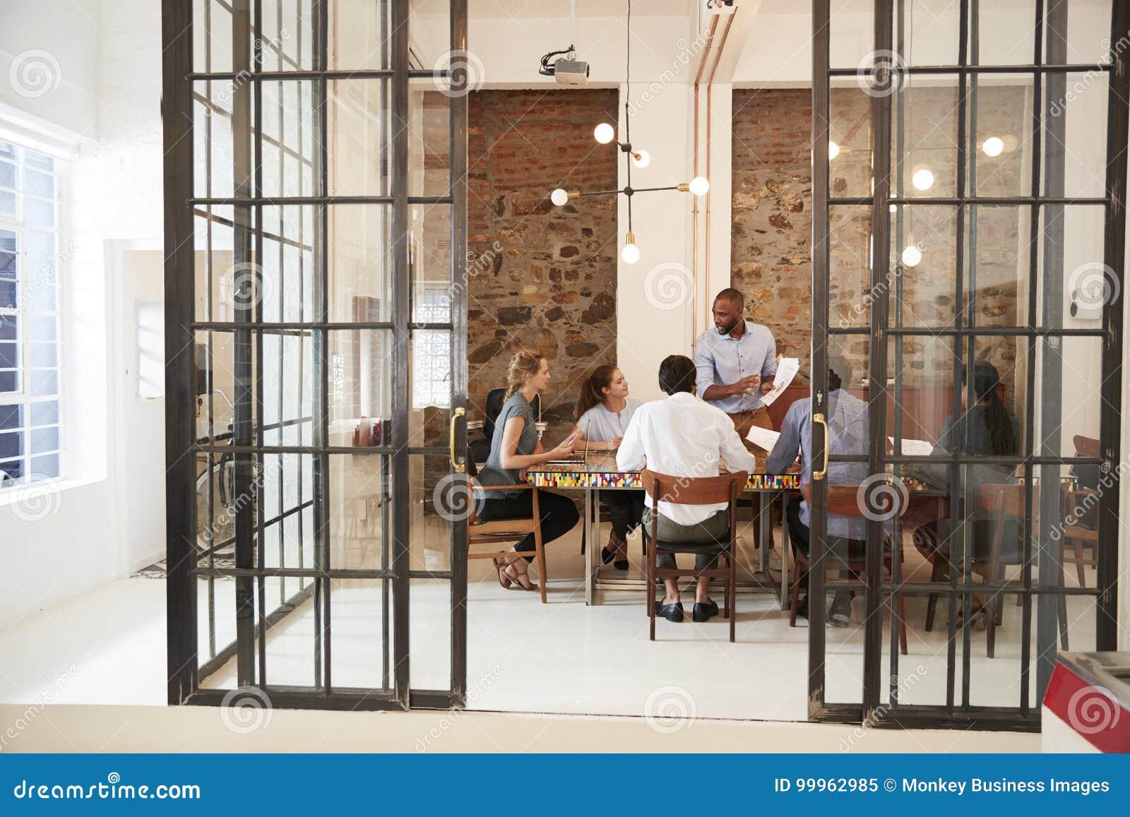 Homem negro novo que dá a apresentação em uma sala de reunião