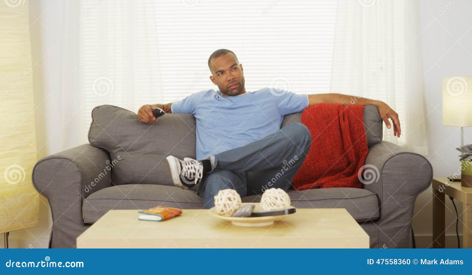 Homem negro que senta-se no sofá que olha a tevê