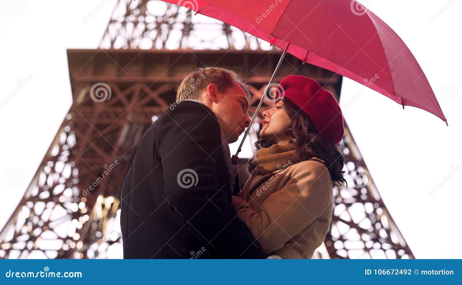 Homem no amor aproximadamente para beijar a mulher bonita sob o guarda-chuva, data romântica em Paris