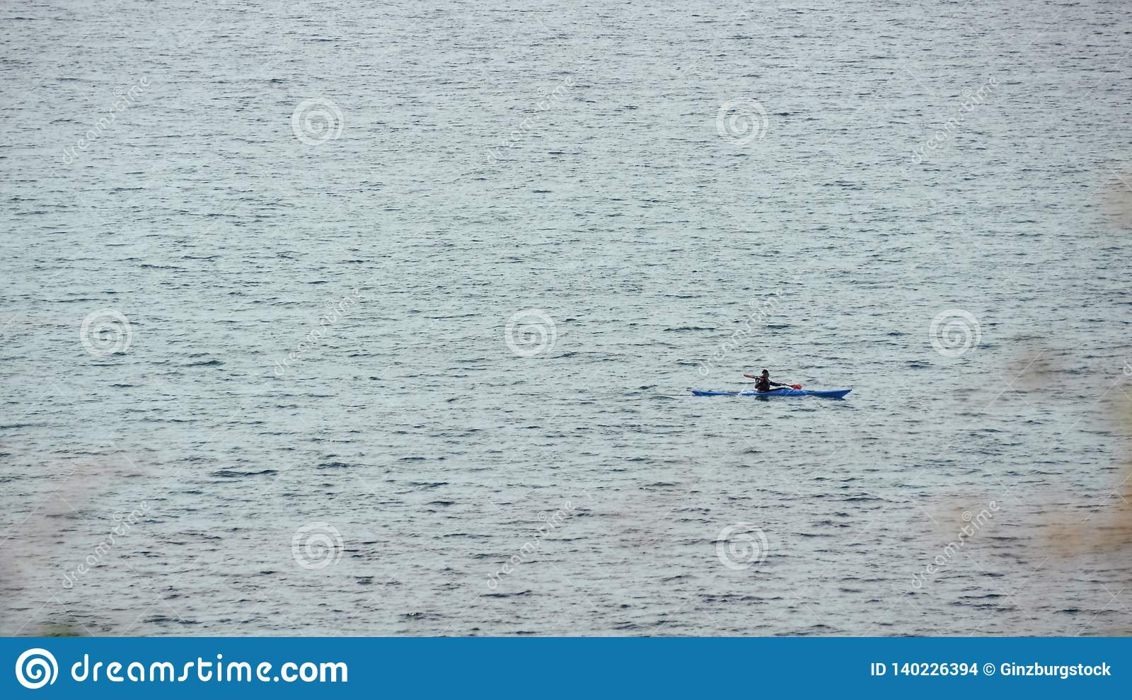 Homem no barco de fileira no mar aberto