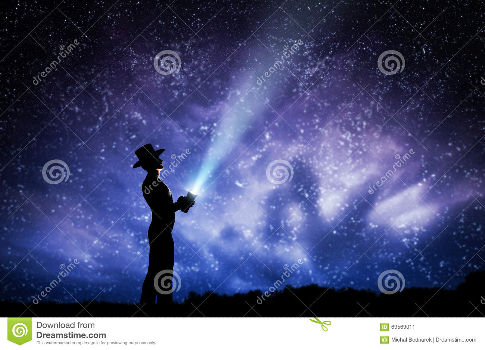 Homem no chapéu que joga o feixe luminoso acima do céu noturno completamente das estrelas Para explorar, para sonhar, mágica