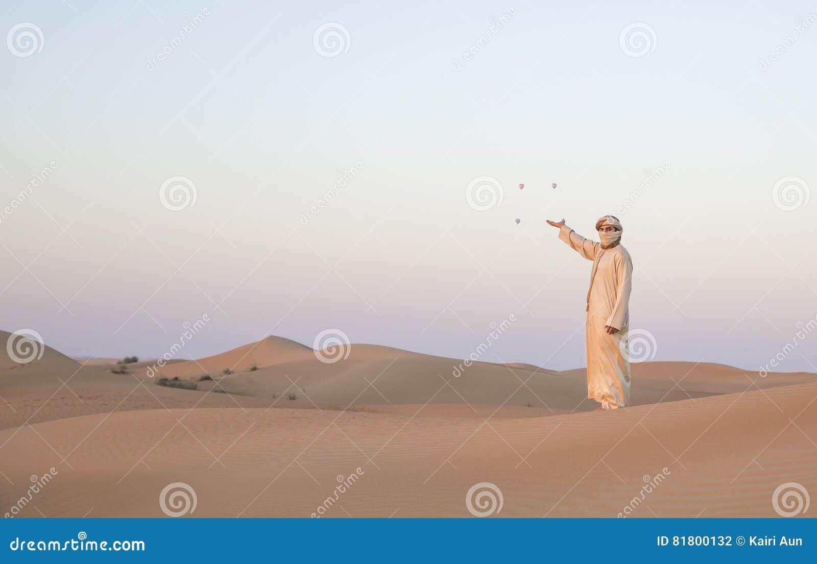 Homem no equipamento tradicional em um deserto perto de Dubai