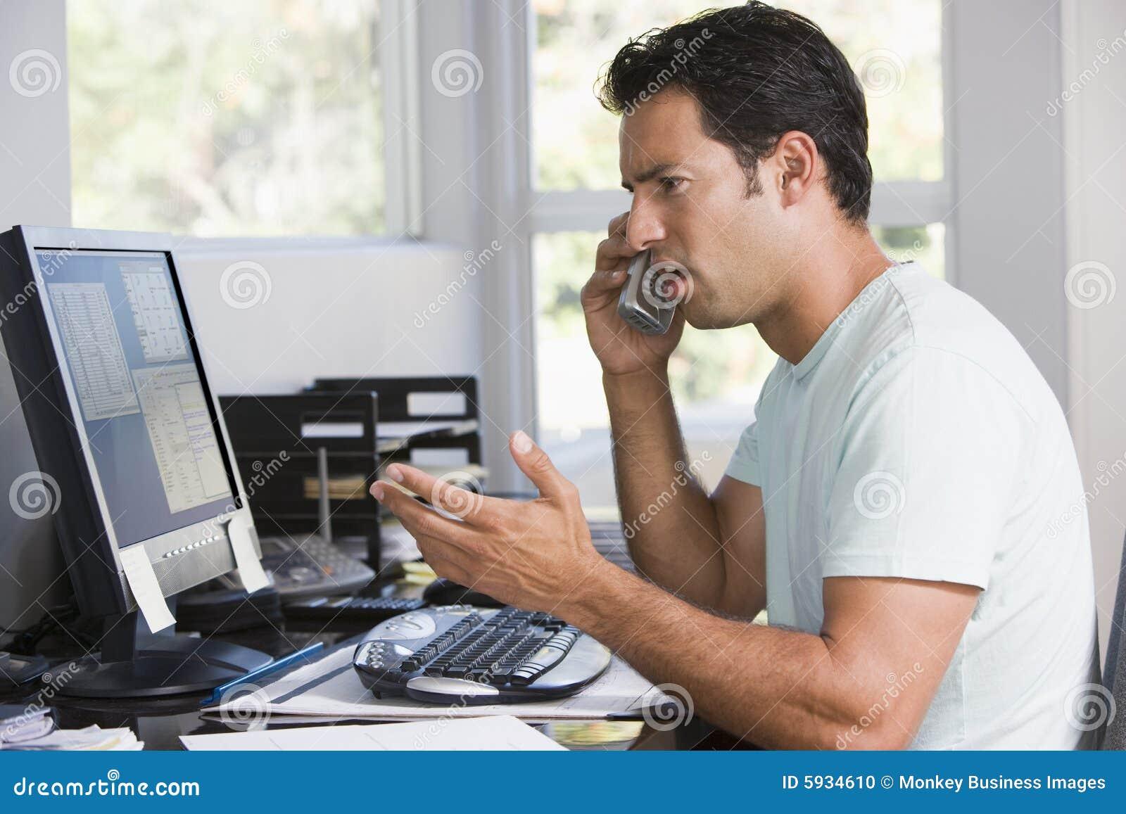 Homem no escritório home no telefone usando o computador