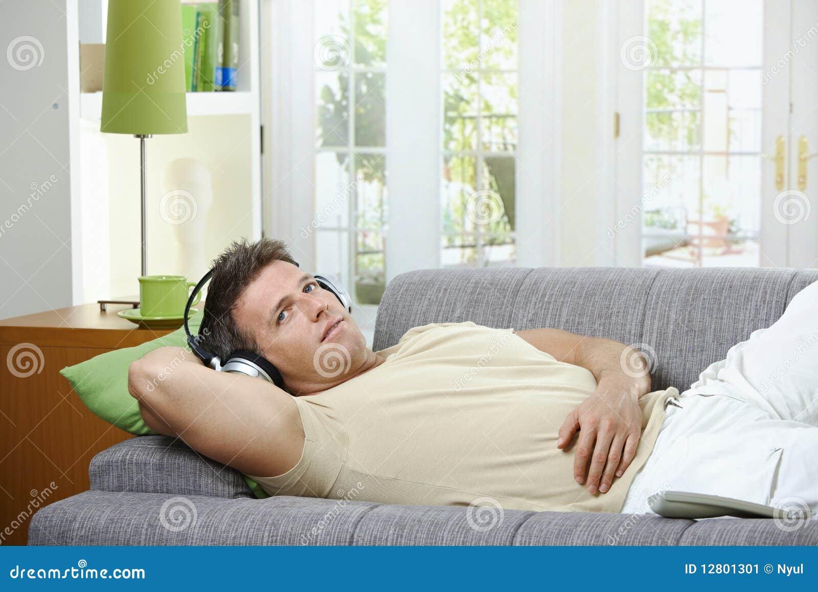 Homem no sofá que escuta o sorriso da música