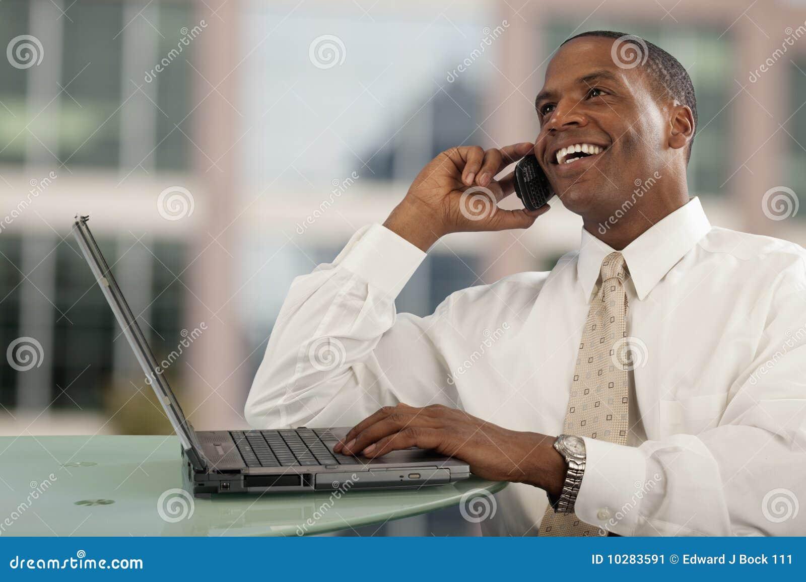 Homem no telefone e no computador de pilha