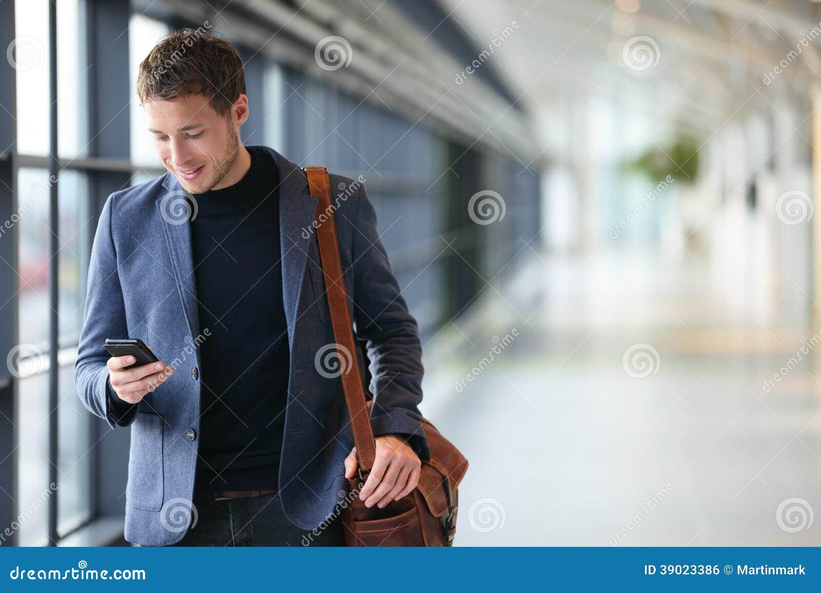 Homem no telefone esperto - homem de negócio novo no aeroporto