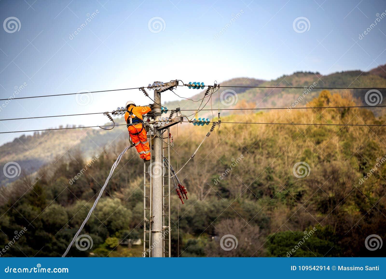 Homem no trabalho O técnico está reparando sistemas de transmissão de alta tensão nos polos de poder