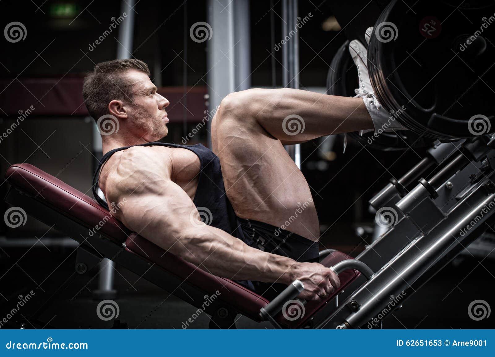 Homem no treinamento do gym na imprensa do pé