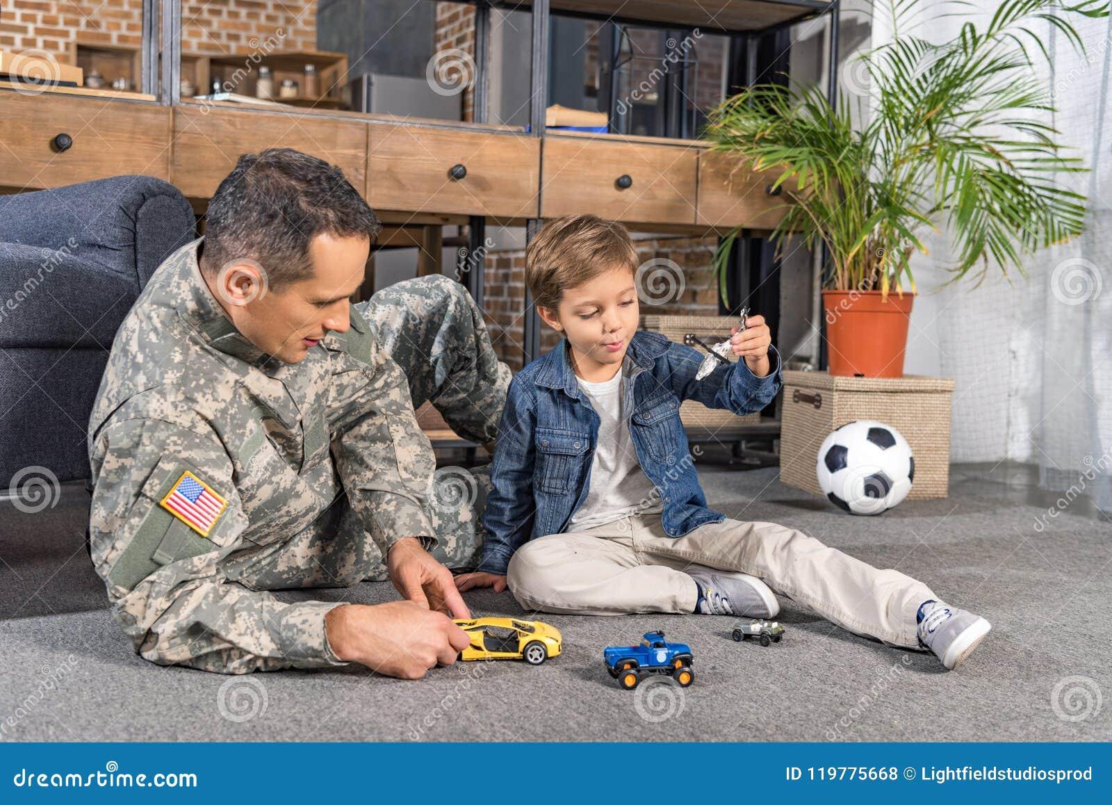Homem no uniforme militar e no filho pequeno que jogam com brinquedos junto