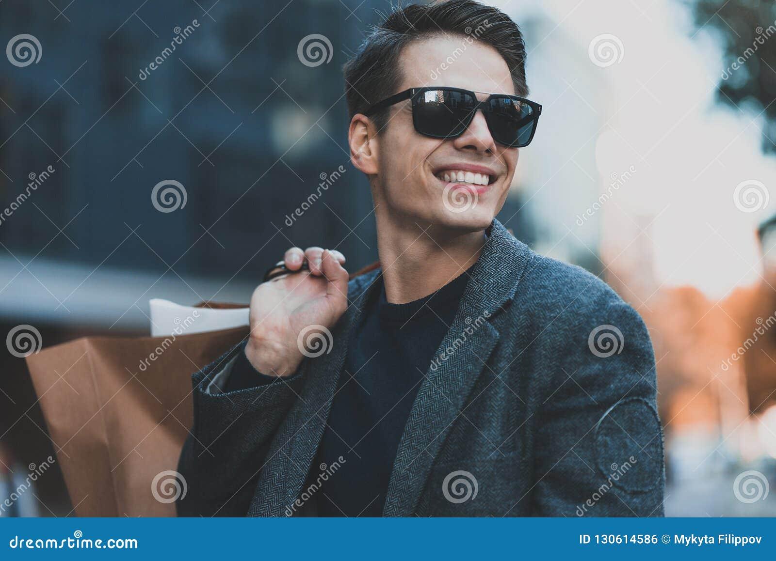 Indivíduo fresco positivo com óculos de sol e sacos de papel que anda perto  da mostra com reflexão 93f7a2d982