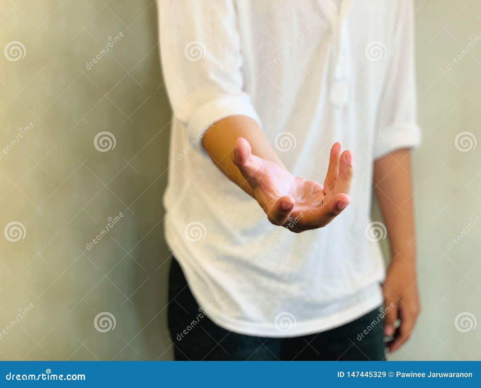 Homem novo aberto e mão vazia estendido na frente do fundo da parede do cimento