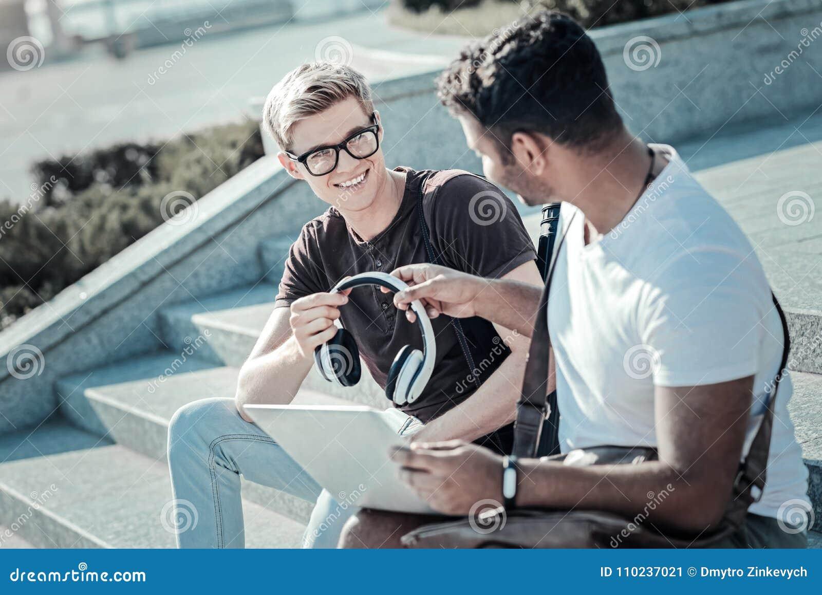 Homem novo agradável que dá fones de ouvido a seu amigo