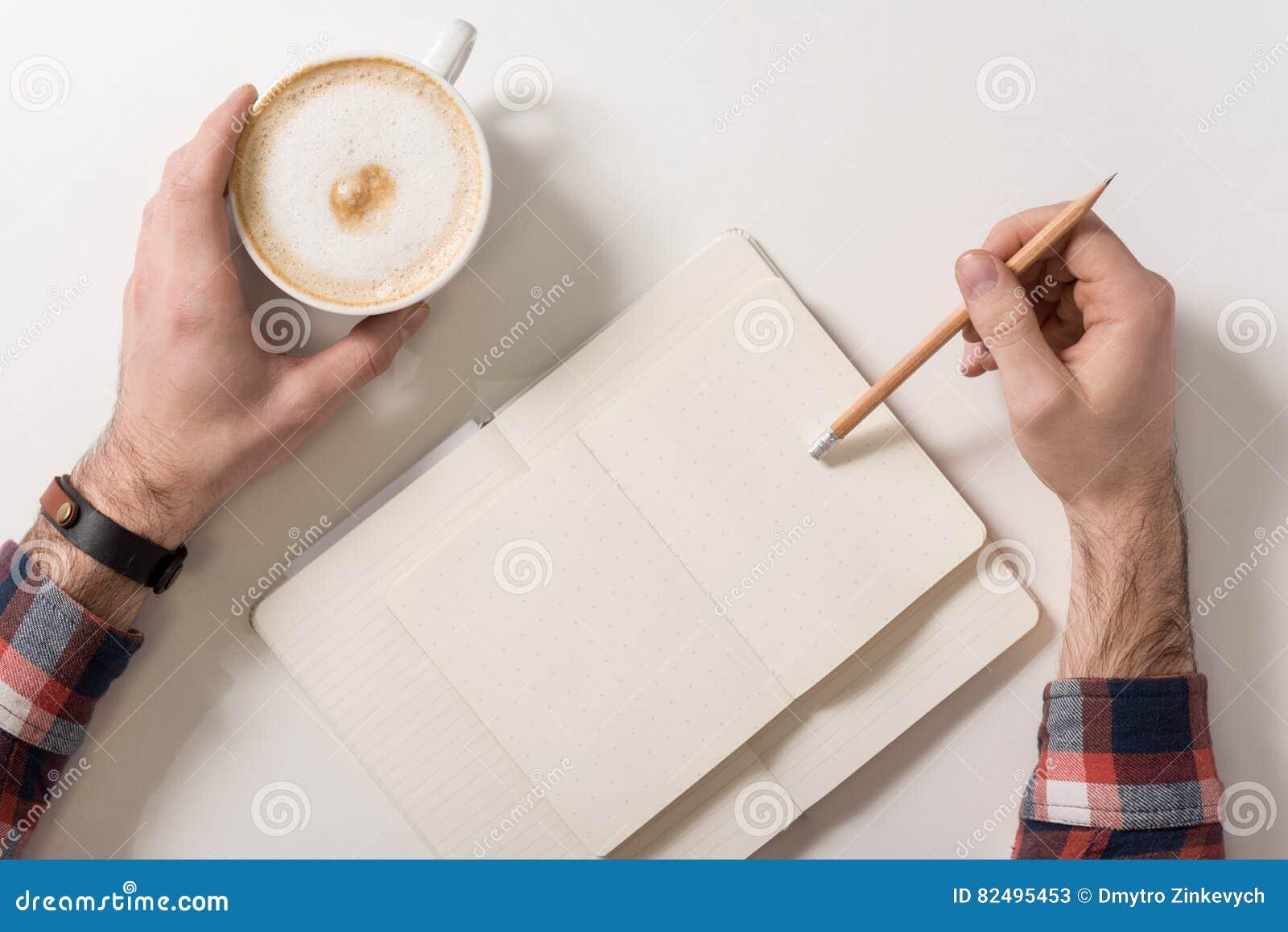 Homem novo agradável que guarda um lápis