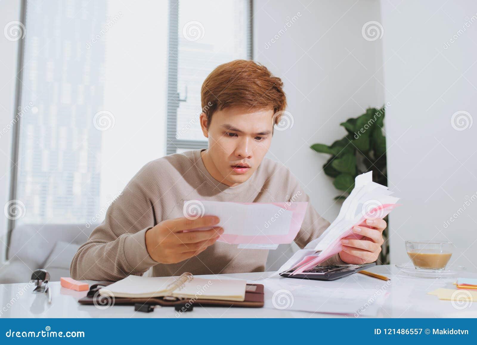 Homem novo asiático que conta usando a calculadora e o esforço no problema