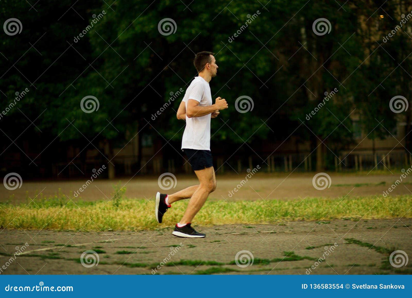 Homem novo atlético que corre na noite da natureza