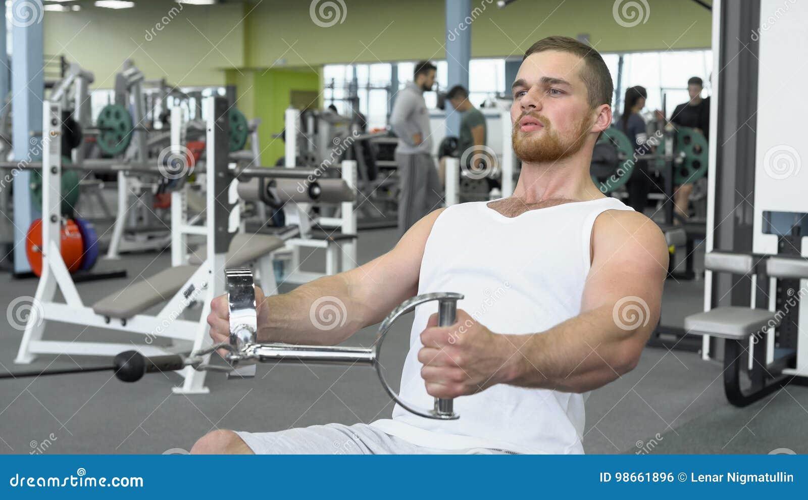Homem novo atlético que exercita em um dispositivo de bloco Retrato do homem atlético forte no treinamento do gym
