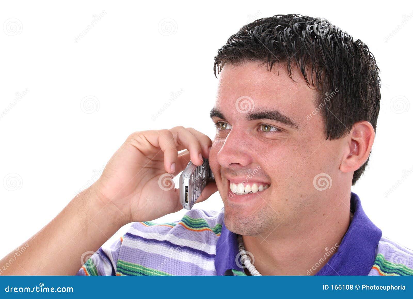 Homem novo atrativo no telemóvel com sorriso