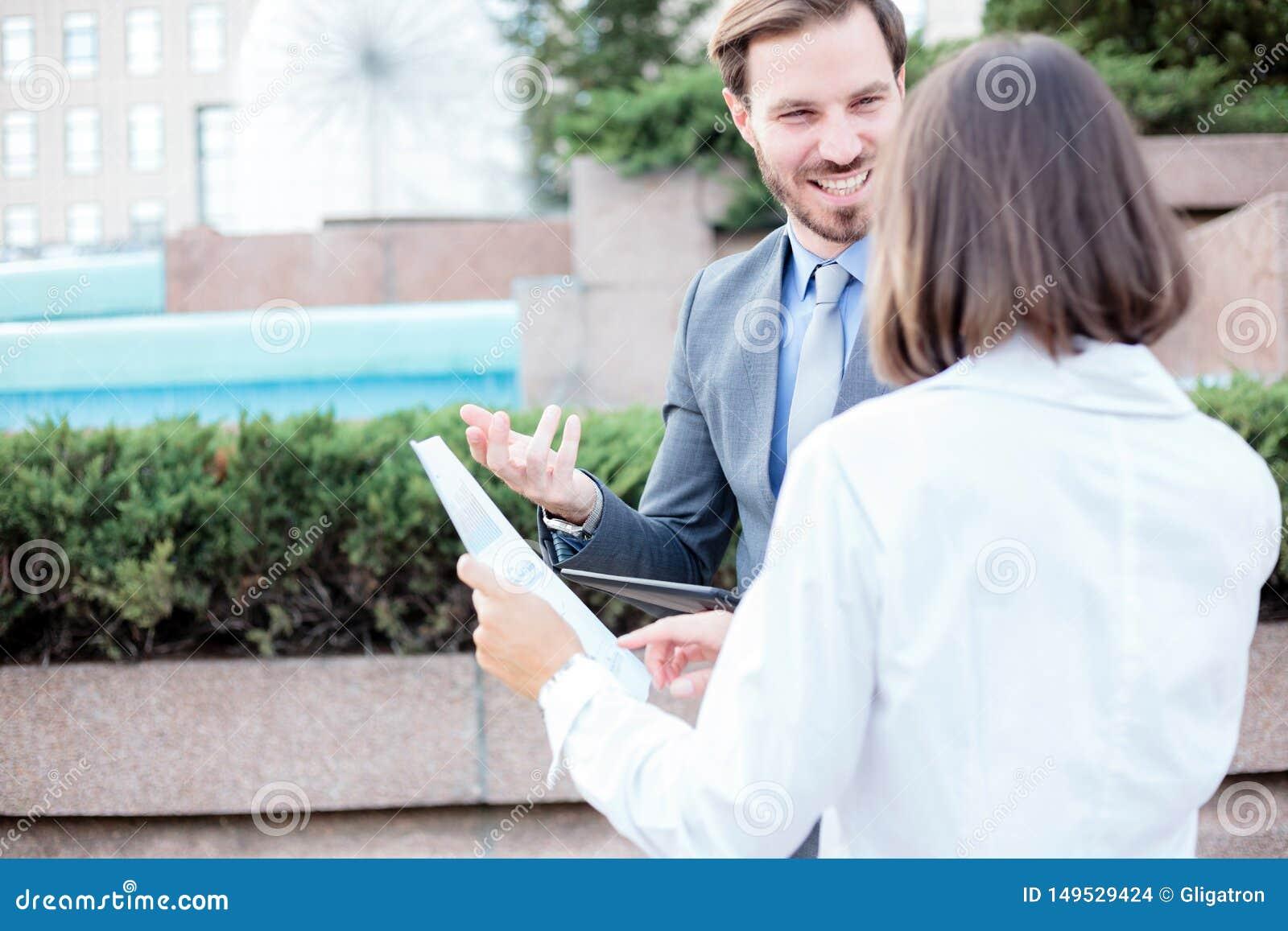 Homem novo bem sucedido e executivos fêmeas que falam na frente de um prédio de escritórios, tendo uma reunião e discutindo
