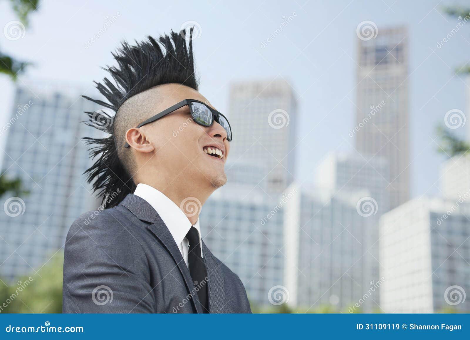 Homem novo bem vestido com Mohawk e óculos de sol que sorriem, arranha-céus no fundo