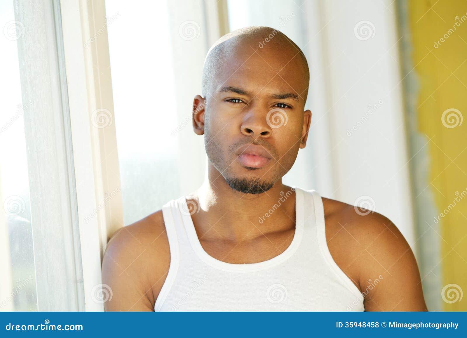 Homem novo bonito que está pela janela
