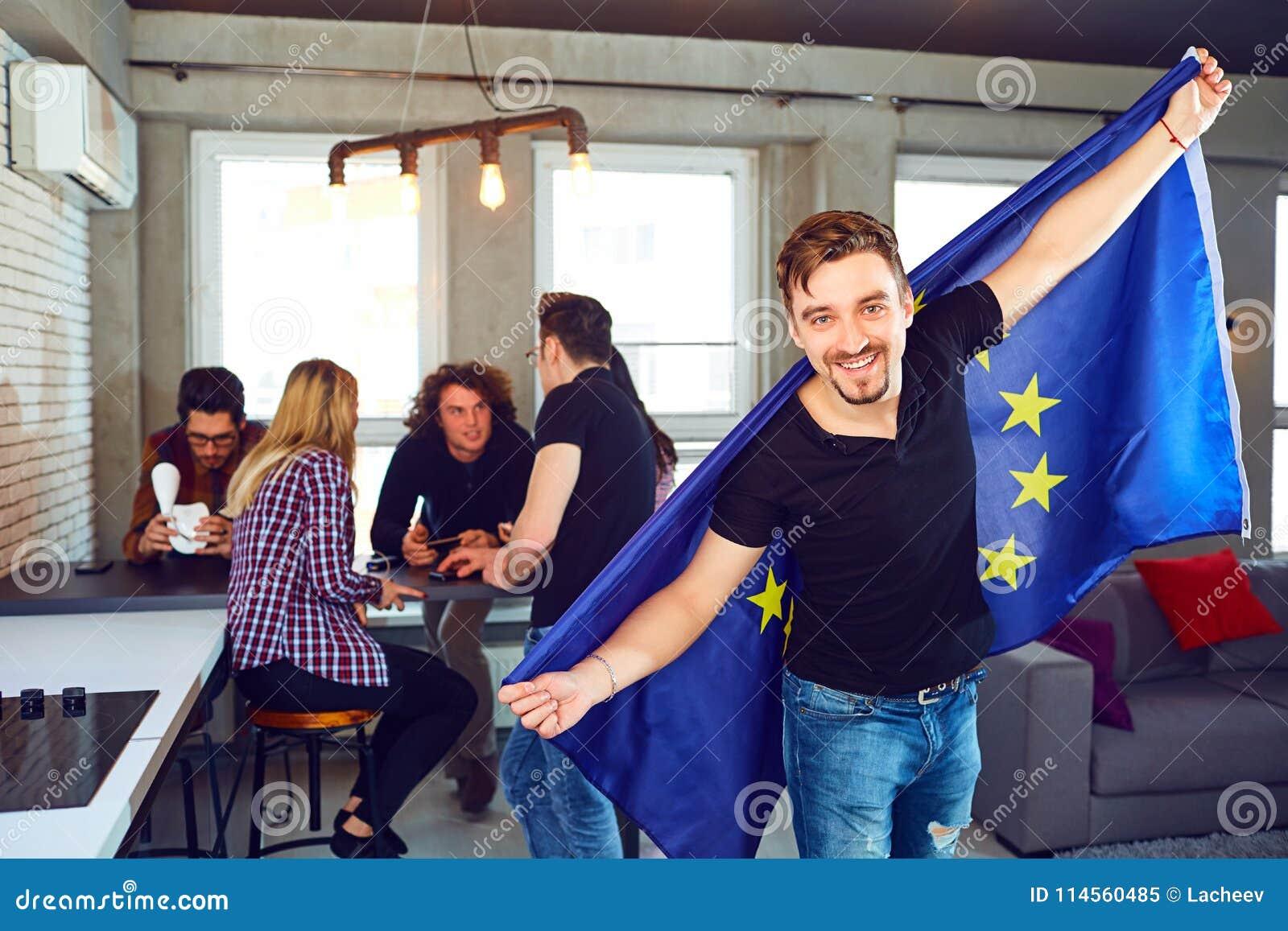 Homem novo com a bandeira europeia em suas mãos na sala