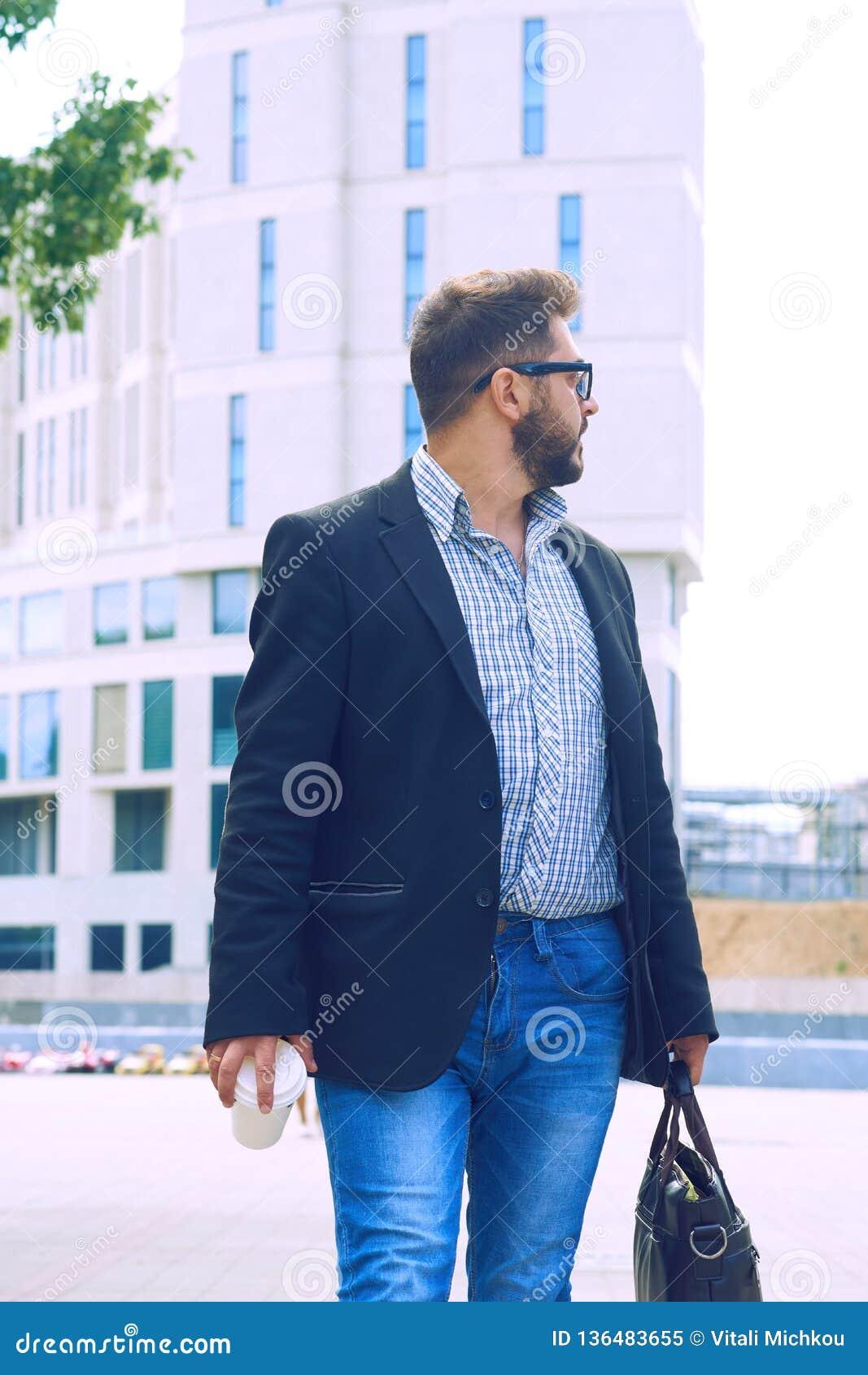 Homem novo com a barba nos vidros que guardam o copo de café e que falam no telefone celular ao andar fora