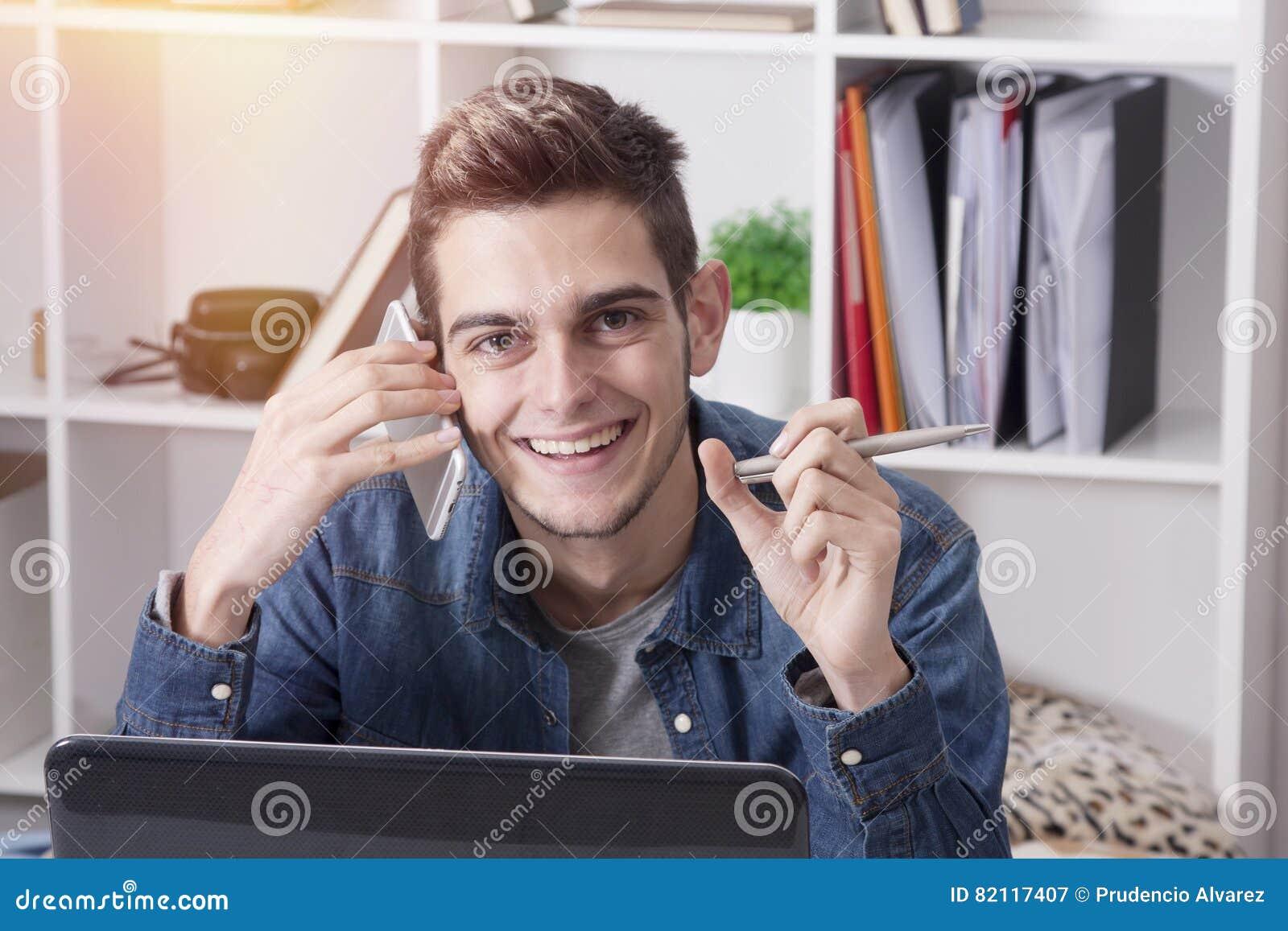 Homem novo com móbil e computador