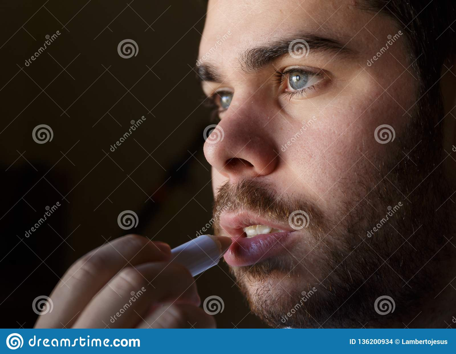 Homem novo com uma barba que repara seus bordos danificados com creme hidratante