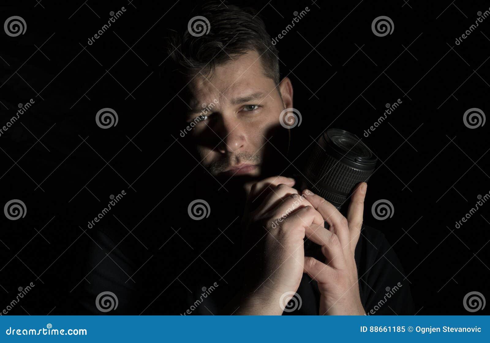 Homem novo como um retrato do fotógrafo isolado no preto