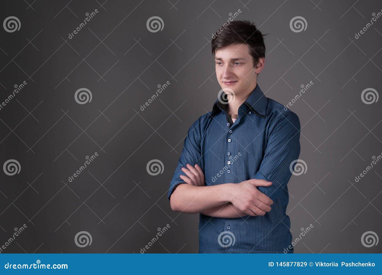 Homem novo considerável na camisa azul que olha afastado com braços cruzados e no fundo cinzento