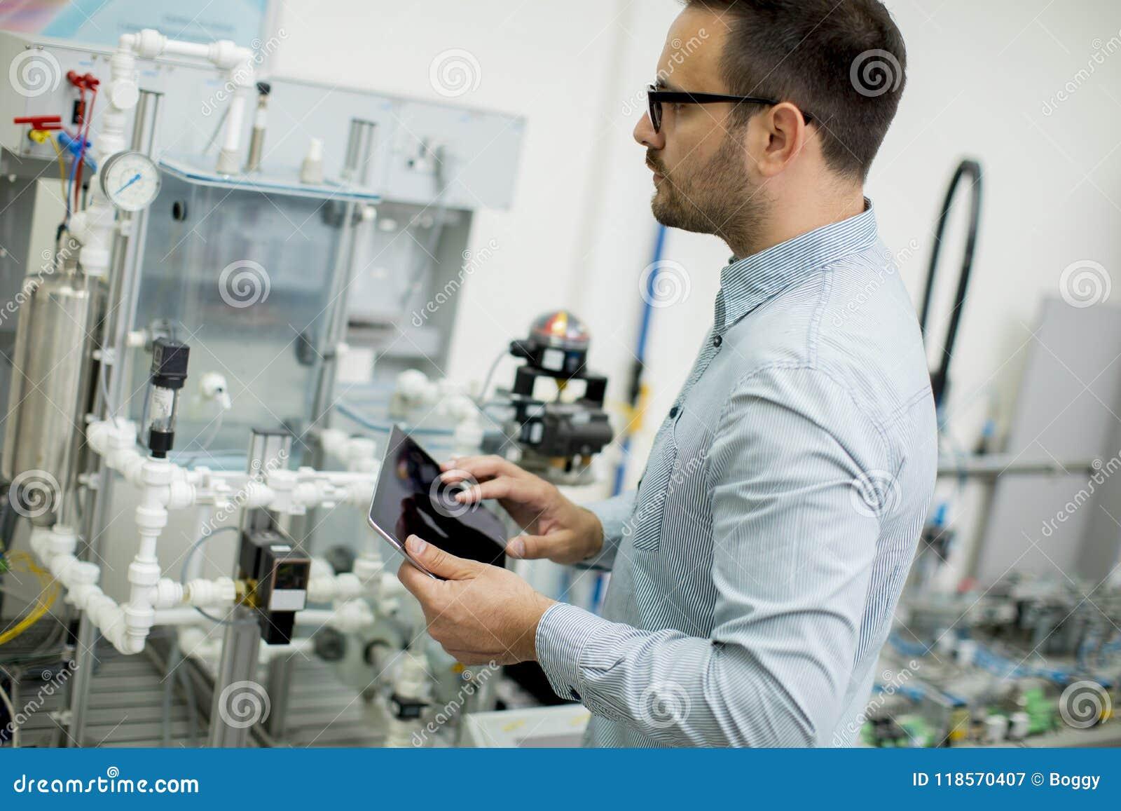 Homem novo considerável na oficina eletrônica que guarda Ta digital