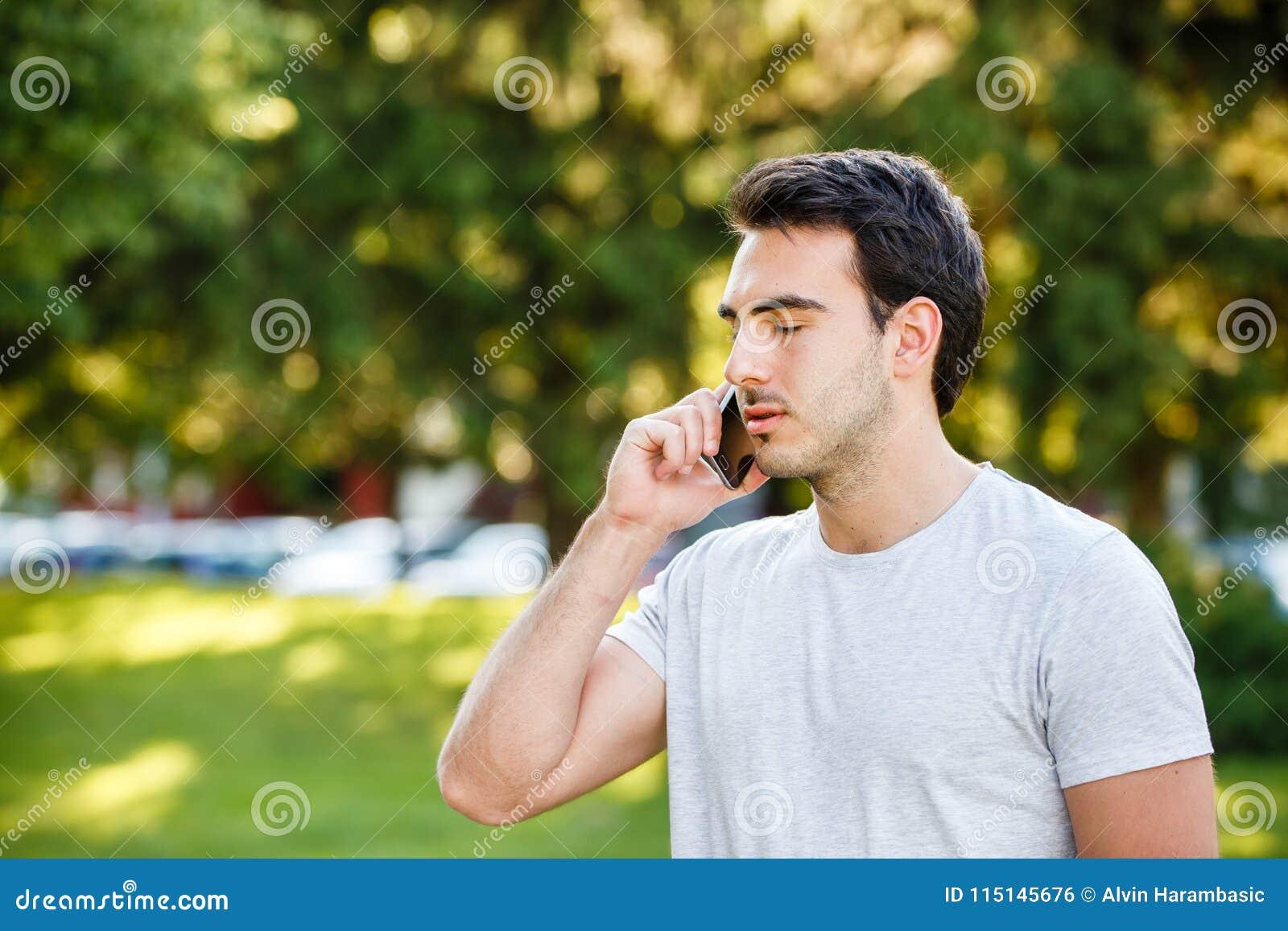 Homem novo considerável no talkig do parque em seu telefone