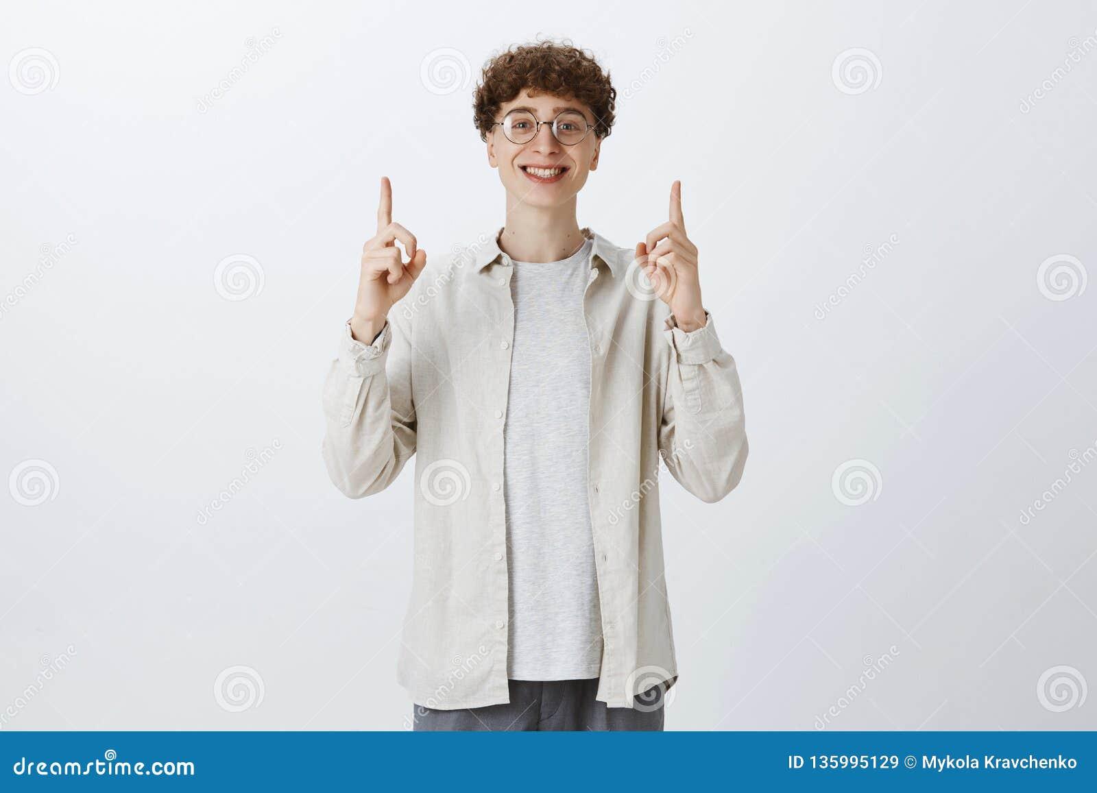 Homem novo considerável novo otimista e emotivo do encantamento em vidros redondos e nas mãos medonhas encaracolados para apontar