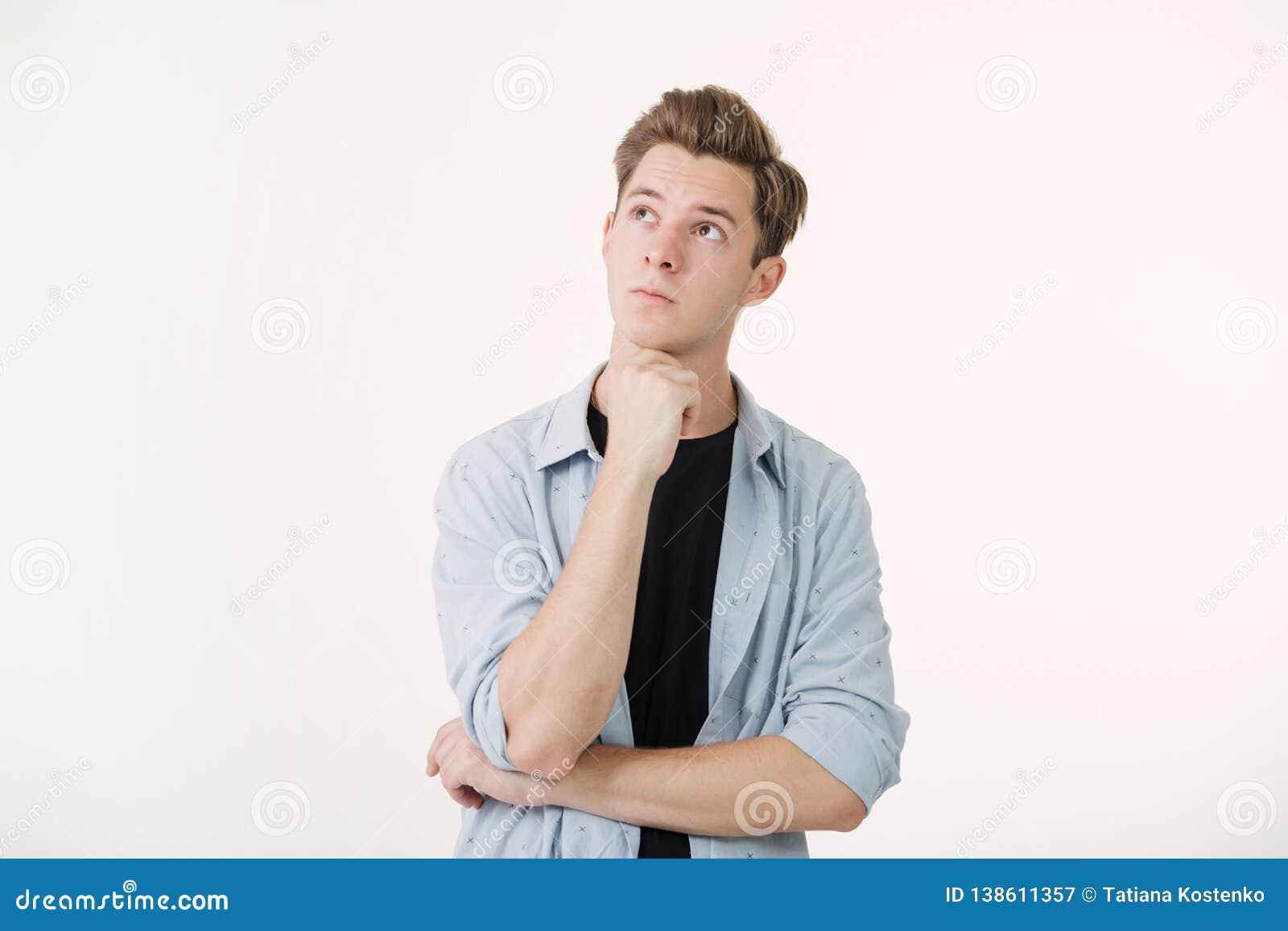 Homem novo considerável pensativo que veste a camisa azul sobre o fundo branco