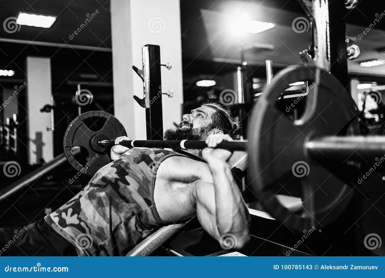 Homem novo considerável que faz o exercício da imprensa de banco no gym