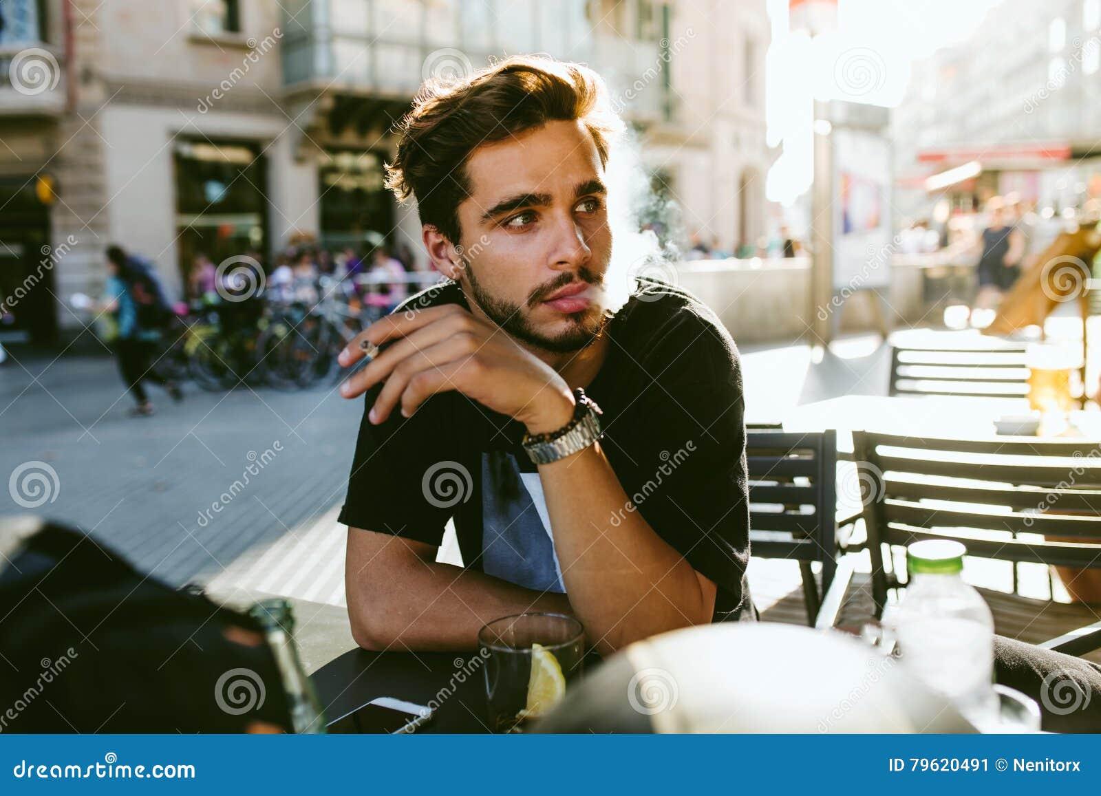 Homem novo considerável que fuma na rua