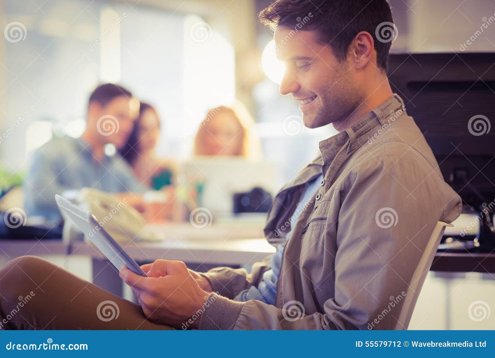 Homem novo de sorriso que usa a tabuleta digital