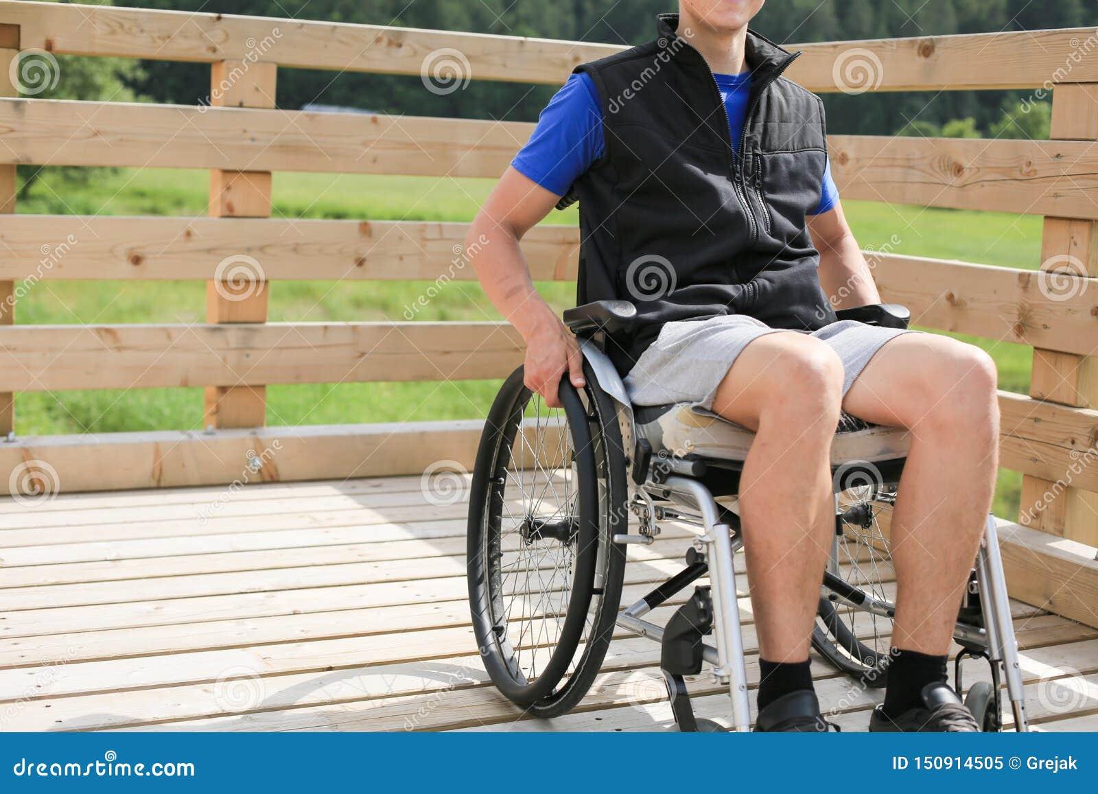Homem novo deficiente em uma cadeira de rodas