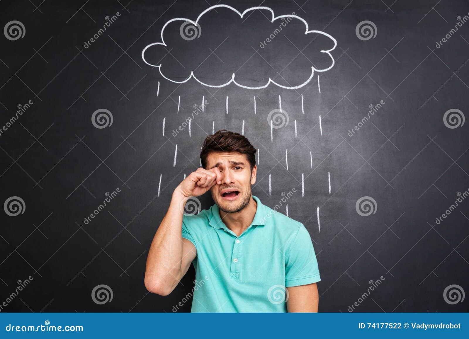 Homem novo desapontado infeliz que grita sob a chuva tirada