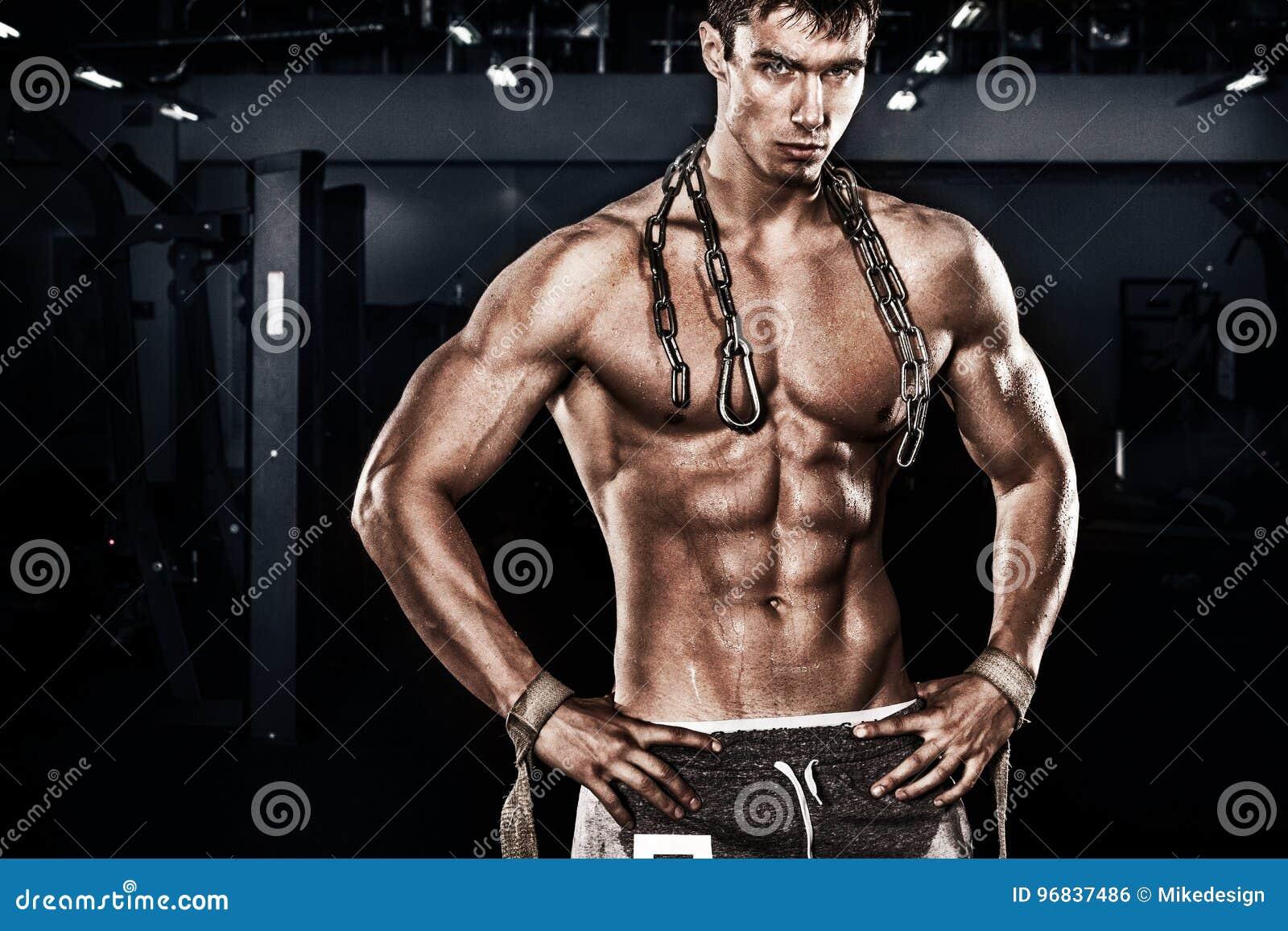 Homem novo descamisado atlético dos esportes - o modelo da aptidão guarda as correntes no gym Copie a frente do espaço seu texto