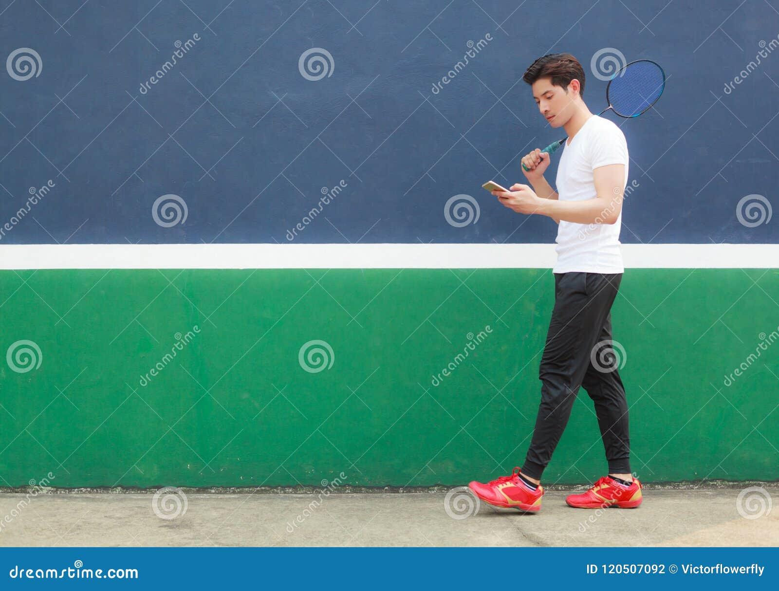 Homem novo do atleta que trabalha no smartphone ao andar no clube de esporte Escritório móvel, autônomo, estilo de vida, mercado