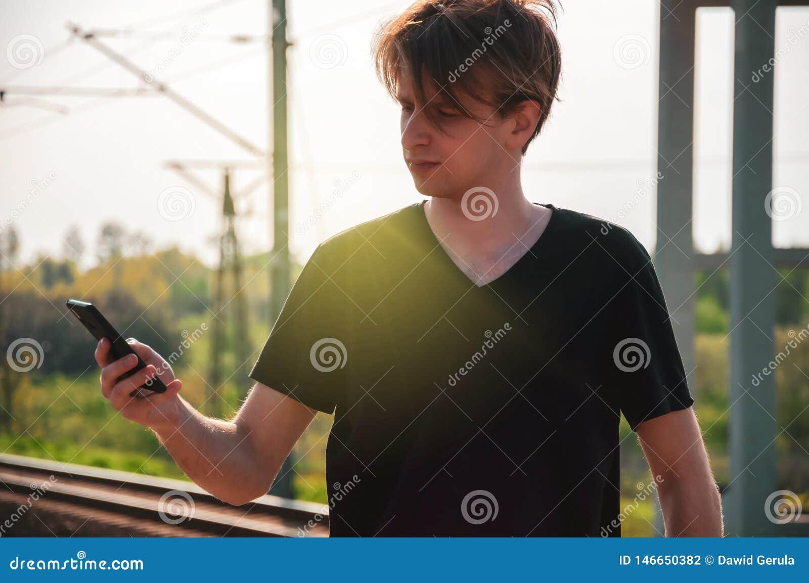 Homem novo do viajante que fala atrav?s do telefone na esta??o de trem durante o tempo quente do ver?o, fazendo gestos ao falar