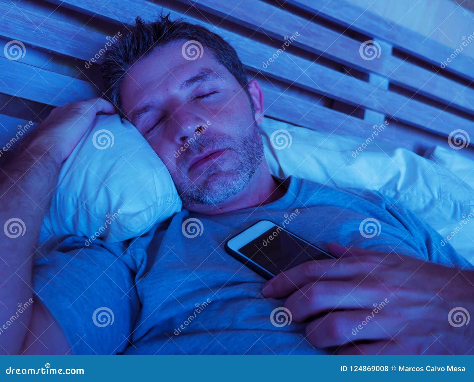 Homem novo do viciado do Internet que dorme na cama que guarda o telefone celular em sua mão na noite no smartphone e no uso exce